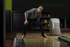Smiling young man playing with a bowling ball Stock Photos