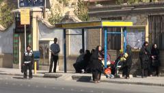 Iran, bus stop, public transport, women in chadors waiting Stock Footage