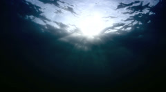 Light rays penetrating ocean surface, dreamy underwater scene - stock footage