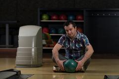 Stock Photo of cheerful young man holding bowling ball