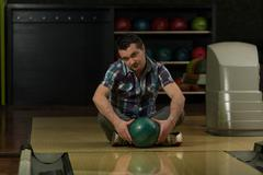 cheerful young man holding bowling ball - stock photo