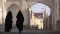 Stock Video Footage of Iran, two veiled ladies in black chadors walk through old city