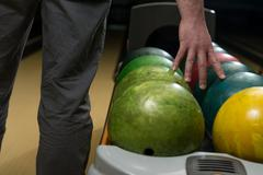 holding ball against bowling alley - stock photo