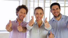 Gleeful colleagues showing thumbs up to camera Stock Footage