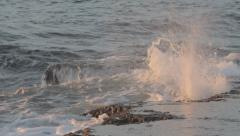 Waves hitting rock during the golden hour before sunset Stock Footage