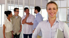 Content blonde businesswoman posing in front of her colleagues Stock Footage