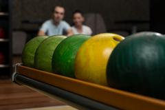 beautiful cheerful couple talking at the bowling alley - stock photo