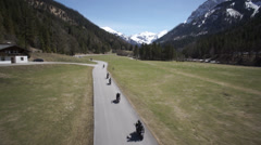 Bikers riding motorbike on country road in Eng, Austria Stock Footage