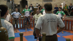 Tourists watch zurkhaneh performance inside gymnasium in Iran - stock footage