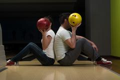 young couple hiding their faces behind bowling ball - stock photo