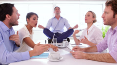 Businessman meditating while his colleagues are arguing Stock Footage
