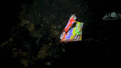 Plastic food wrapper floating underwater at night Stock Footage