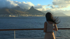 Girl watching the Cape Town peninsula from a ship at sea at sunset Stock Footage