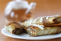 Pancakes stuffed with mushrooms and cabbage Stock Photos