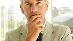 Thinking businessman looking at camera - stock footage