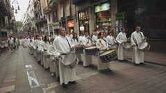 Drum band in ritual clothing marching along the street of Barcelona Stock Footage