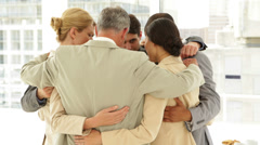 Business people hugging each other in a circle - stock footage