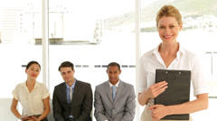 Businesswoman giving thumbs to camera in front of job applicants Stock Footage