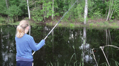 Girl in cool summer day standing at the pond pulls rod Stock Footage