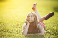 Teenage girl relaxing on grass Stock Photos