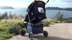 Back of pushchair against sea view Stock Footage