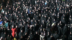 Iran, crowds of women in black chadors walk through streets in parade Stock Footage