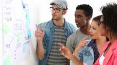 Creative team brainstorming together looking at whiteboard Stock Footage