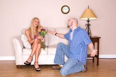 Couple: man apologizes with flowers Stock Photos