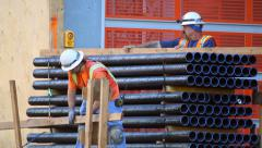 Construction workers prepare pile of pipes at development site Stock Footage