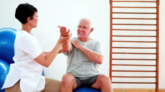 Smiling physiotherapist helping elderly patient stretch arm Stock Footage
