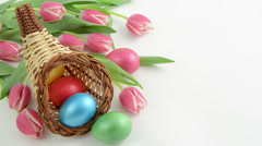 Zoom of cornucopia basket with bunch of pink tulips and Easter eggs Stock Footage