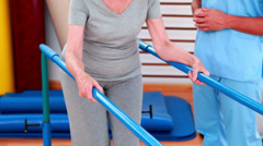 Physical therapist watching patient walk with parallel bars Stock Footage