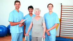 Stock Video Footage of Elderly woman smiling with her physical rehab team