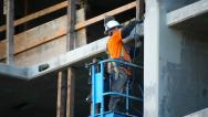 Stock Video Footage of Construction worker takes measurement and polishes the wall at development site