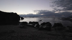Low, Wide angle shot of waves breaking on a rocky shoreline during sunset Stock Footage