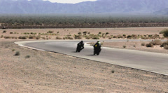 Multiple Superbikes Racing Long shot into turn Stock Footage