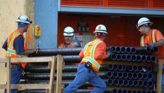 Construction workers unload pipes at development site Stock Footage