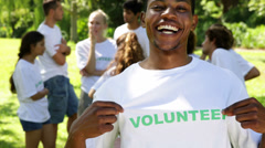 Stock Video Footage of Handsome volunteer showing his tshirt to camera