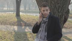 Smiling man using a mobile phone in a park. Stock Footage