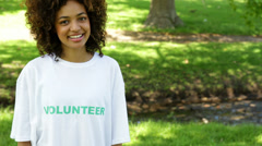 Pretty volunteer smiling at the camera and pointing to tshirt Stock Footage