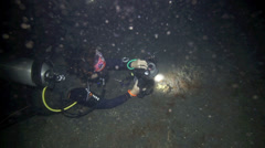 Scuba diver taking underwater photos at night Stock Footage