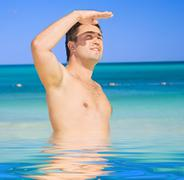 happy tanned man on the beach - stock illustration