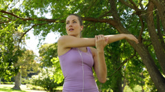 Runner stretching arms listening to music in the park Stock Footage