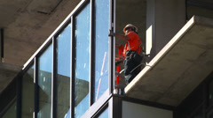 Construction workers install glass window at development site - stock footage