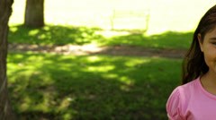 Smiling little girl wearing pink for breast cancer awareness in the park Stock Footage
