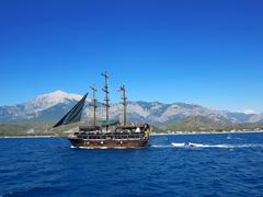 kemer, turkey - 14.06.2013: ship with tourists swimming in the sea on a backg - stock photo