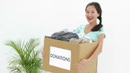Stock Video Footage of Pretty brunette holding donation box full of clothes