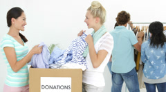 Team of people going through donation box of clothes Stock Footage