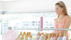 Attractive fashion designer looking through her clothing rail - stock footage