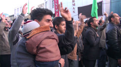 Stock Video Footage of Iran, father holds child in sombre religious parade